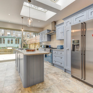 Photo of a large traditional galley kitchen/diner in London with a submerged sink, shaker cabinets, blue cabinets, grey splashback, stainless steel appliances, porcelain flooring, an island, beige floors and grey worktops.