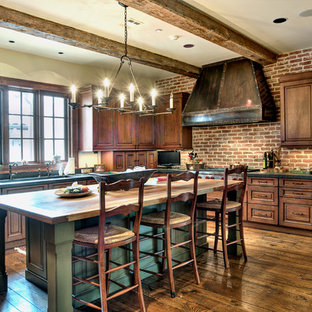 Geschlossene, Große Mediterrane Küche in L-Form mit Unterbauwaschbecken, profilierten Schrankfronten, dunklen Holzschränken, Speckstein-Arbeitsplatte, Küchenrückwand in Rot, Rückwand aus Backstein, Elektrogeräten mit Frontblende, dunklem Holzboden, Kücheninsel, braunem Boden und roter Arbeitsplatte in Houston