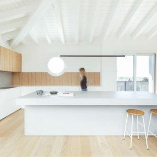 Foto di una grande cucina minimal chiusa con ante lisce, ante bianche, top in legno, paraspruzzi grigio, elettrodomestici neri, parquet scuro, pavimento marrone e top bianco