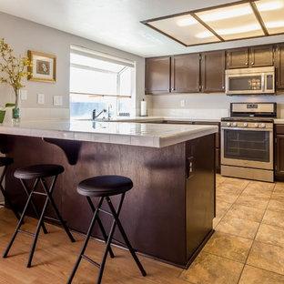 中くらいのエクレクティックスタイルのおしゃれなキッチン (アンダーカウンターシンク、落し込みパネル扉のキャビネット、茶色いキャビネット、タイルカウンター、黄色いキッチンパネル、磁器タイルのキッチンパネル、シルバーの調理設備、セメントタイルの床、マルチカラーの床、白いキッチンカウンター) の写真