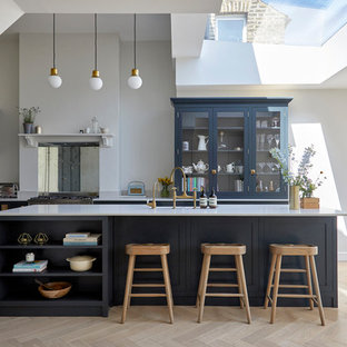 This is an example of a medium sized contemporary l-shaped open plan kitchen in London with blue cabinets, mirror splashback, stainless steel appliances, light hardwood flooring, an island, white worktops, shaker cabinets and beige floors.