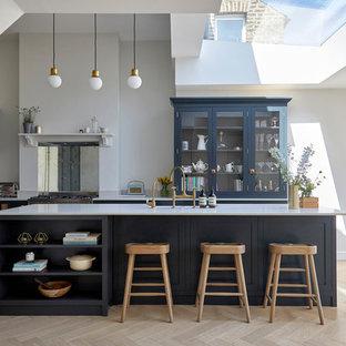 ロンドンの中くらいのコンテンポラリースタイルのおしゃれなキッチン (青いキャビネット、ミラータイルのキッチンパネル、シルバーの調理設備、淡色無垢フローリング、白いキッチンカウンター、シェーカースタイル扉のキャビネット、ベージュの床) の写真