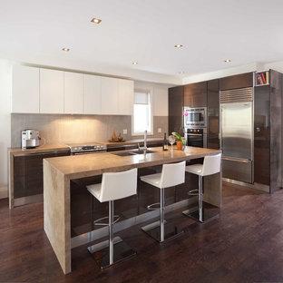 Diseño de cocina en L, moderna, con armarios con paneles lisos, puertas de armario de madera en tonos medios, salpicadero verde y salpicadero de piedra caliza