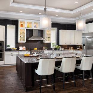 Idéer för vintage l-kök, med en undermonterad diskho, skåp i shakerstil, vita skåp, granitbänkskiva, svart stänkskydd, stänkskydd i keramik, rostfria vitvaror, mörkt trägolv och en köksö