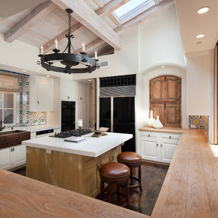 Southwestern kitchen inspiration - Inspiration for a southwestern galley dark wood floor kitchen remodel in San Diego with a farmhouse sink, raised-panel cabinets, white cabinets, multicolored backsplash, black appliances and an island