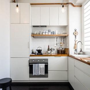 Idee per una cucina a L nordica con lavello da incasso, ante lisce, ante bianche, top in legno, paraspruzzi bianco, paraspruzzi con piastrelle diamantate, elettrodomestici neri, pavimento nero e top marrone