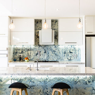 Contemporary galley kitchen in Sydney with an undermount sink, flat-panel cabinets, white cabinets, metallic splashback, white appliances, with island, brown floor and grey benchtop.