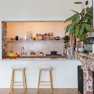 Design ideas for a bohemian galley kitchen in London with a submerged sink, quartz worktops, white splashback, light hardwood flooring, a breakfast bar, brown floors and white worktops.