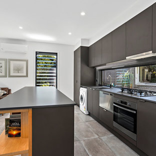 Design ideas for a small beach style galley open plan kitchen in Other with a drop-in sink, flat-panel cabinets, window splashback, stainless steel appliances, with island, black benchtop, grey cabinets, quartz benchtops, grey splashback, ceramic floors and beige floor.