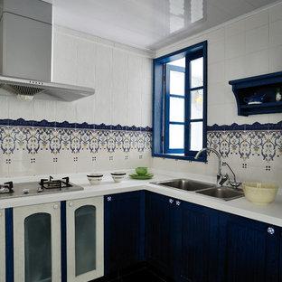 На фото: кухня в средиземноморском стиле с накладной раковиной, синими фасадами и разноцветным фартуком с