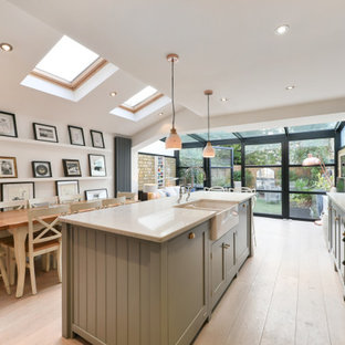 Inspiration for a traditional kitchen/diner in London with a belfast sink, shaker cabinets, grey cabinets, light hardwood flooring, an island, beige floors and white worktops.