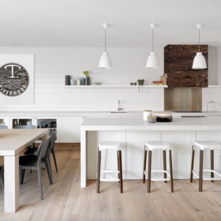 Photo of a large contemporary galley eat-in kitchen in Melbourne with an undermount sink, glass-front cabinets, white cabinets, white splashback, timber splashback, light hardwood floors, an island and beige floor.
