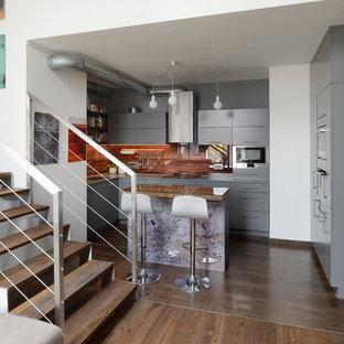 他の地域の中くらいのインダストリアルスタイルのおしゃれなキッチン (一体型シンク、フラットパネル扉のキャビネット、グレーのキャビネット、御影石カウンター、オレンジのキッチンパネル、ガラス板のキッチンパネル、シルバーの調理設備、セラミックタイルの床) の写真
