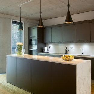 Immagine di una cucina parallela industriale con lavello sottopiano, ante lisce, ante marroni, paraspruzzi bianco, elettrodomestici in acciaio inossidabile, pavimento in legno massello medio e isola