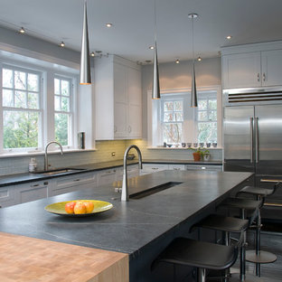 This is an example of a large contemporary u-shaped eat-in kitchen in Philadelphia with recessed-panel cabinets, white cabinets, white splashback, stainless steel appliances, glass tile splashback, with island, an undermount sink, soapstone benchtops and black benchtop.