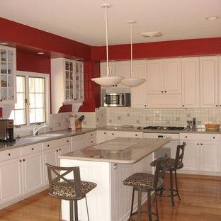 Mittelgroße Klassische Wohnküche in U-Form mit Doppelwaschbecken, profilierten Schrankfronten, weißen Schränken, Quarzwerkstein-Arbeitsplatte, Küchenrückwand in Weiß, Rückwand aus Porzellanfliesen, weißen Elektrogeräten, braunem Holzboden, Kücheninsel und braunem Boden in Grand Rapids