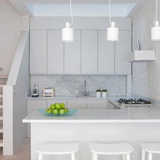 Idéer för ett litet modernt l-kök, med en undermonterad diskho, släta luckor, stänkskydd i sten, ljust trägolv och en halv köksö
