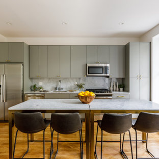Contemporary kitchen appliance - Inspiration for a contemporary medium tone wood floor kitchen remodel in New York with an undermount sink, flat-panel cabinets, gray cabinets, white backsplash, stone slab backsplash, stainless steel appliances and white countertops