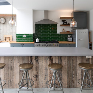 Inspiration for a mid-sized industrial single-wall kitchen in Other with a farmhouse sink, recessed-panel cabinets, grey cabinets, green splashback, subway tile splashback, stainless steel appliances, concrete floors, with island, grey floor and wood benchtops.