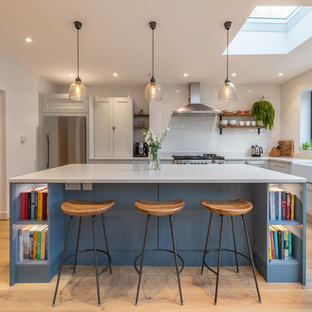 This is an example of a traditional l-shaped kitchen in Sussex with a belfast sink, shaker cabinets, grey cabinets, white splashback, metro tiled splashback, light hardwood flooring, an island, beige floors and white worktops.