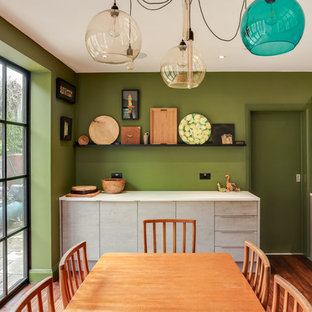 Design ideas for a medium sized bohemian kitchen/diner in London with a single-bowl sink, flat-panel cabinets, grey cabinets, laminate countertops, multi-coloured splashback, glass tiled splashback, coloured appliances, dark hardwood flooring, an island, brown floors and multicoloured worktops.