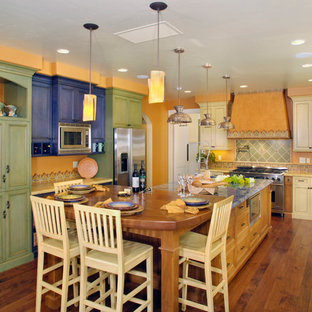 Photo of an eclectic u-shaped kitchen/diner in San Francisco with a belfast sink, recessed-panel cabinets, green cabinets, multi-coloured splashback and stainless steel appliances.