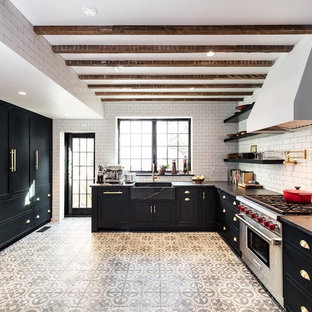 Mid-sized farmhouse eat-in kitchen appliance - Example of a mid-sized country l-shaped cement tile floor and brown floor eat-in kitchen design in DC Metro with a farmhouse sink, shaker cabinets, black cabinets, white backsplash, subway tile backsplash, stainless steel appliances and no island