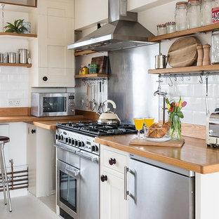 ロンドンのインダストリアルスタイルのおしゃれなコの字型キッチン (エプロンフロントシンク、シェーカースタイル扉のキャビネット、ベージュのキャビネット、木材カウンター、白いキッチンパネル、サブウェイタイルのキッチンパネル、シルバーの調理設備の) の写真