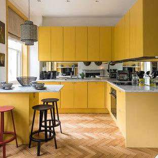 Cette image montre une petite cuisine nordique en L avec un évier encastré, un placard à porte plane, des portes de placard jaunes, une crédence en carreau de miroir, un sol en bois brun et une péninsule.