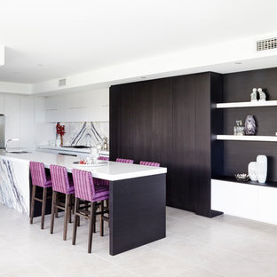 Inspiration for a large contemporary l-shaped kitchen in Sydney with a double-bowl sink, flat-panel cabinets, white cabinets, quartz benchtops, white splashback, stone slab splashback, stainless steel appliances, with island, white benchtop and grey floor.