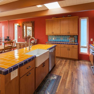 Large midcentury l-shaped open plan kitchen in San Luis Obispo with a farmhouse sink, flat-panel cabinets, medium wood cabinets, tile benchtops, blue splashback, ceramic splashback, stainless steel appliances, medium hardwood floors and with island.