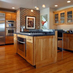 他の地域の中サイズのインダストリアルスタイルのおしゃれなキッチン (シェーカースタイル扉のキャビネット、濃色木目調キャビネット、クオーツストーンカウンター、シルバーの調理設備の、濃色無垢フローリング、茶色い床) の写真