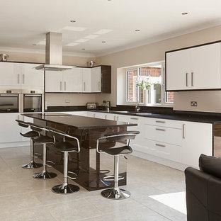 他の地域の広いコンテンポラリースタイルのおしゃれなキッチン (フラットパネル扉のキャビネット、白いキャビネット、シルバーの調理設備、ドロップインシンク、クオーツストーンカウンター、セラミックタイルの床) の写真