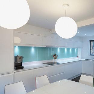 Diseño de cocina comedor en L, moderna, grande, con armarios con paneles lisos, puertas de armario blancas, salpicadero azul, fregadero bajoencimera, encimera de acrílico y suelo de madera oscura