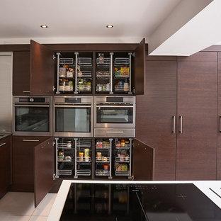 Modelo de cocina comedor actual, extra grande, con armarios con paneles lisos, puertas de armario de madera en tonos medios, electrodomésticos de acero inoxidable, fregadero bajoencimera, encimera de acrílico, suelo de baldosas de porcelana y una isla