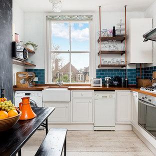 Klassische Wohnküche ohne Insel in L-Form mit Landhausspüle, Kassettenfronten, weißen Schränken, Arbeitsplatte aus Holz, Küchenrückwand in Blau, Rückwand aus Metrofliesen, gebeiztem Holzboden, weißem Boden und brauner Arbeitsplatte in London