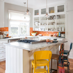 Photo of a transitional u-shaped eat-in kitchen in San Francisco with a farmhouse sink, open cabinets, white cabinets, orange splashback, subway tile splashback, stainless steel appliances, medium hardwood floors, with island and brown floor.