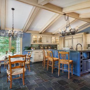 Cette photo montre une grande cuisine américaine nature en L avec un évier de ferme, un placard à porte vitrée, des portes de placard bleues, un plan de travail en quartz modifié, une crédence bleue, une crédence en ardoise, un électroménager en acier inoxydable, un sol en ardoise et un îlot central.