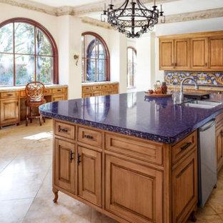 ダラスの広い地中海スタイルのおしゃれなキッチン (セラミックタイルのキッチンパネル、ライムストーンの床、ダブルシンク、レイズドパネル扉のキャビネット、中間色木目調キャビネット、青いキッチンパネル、シルバーの調理設備、青いキッチンカウンター) の写真