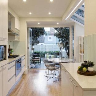 Contemporary eat-in kitchen in Sydney with white cabinets, limestone benchtops, white splashback, ceramic splashback, stainless steel appliances, light hardwood floors and brown floor.