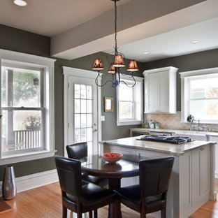 Example of a large trendy u-shaped light wood floor eat-in kitchen design in Chicago with a farmhouse sink, shaker cabinets, white cabinets, marble countertops, orange backsplash, stone tile backsplash, stainless steel appliances and an island