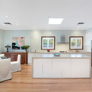 Inspiration for a transitional l-shaped eat-in kitchen in Sydney with an undermount sink, flat-panel cabinets, white cabinets, solid surface benchtops, green splashback, glass sheet splashback, stainless steel appliances, light hardwood floors, with island and beige benchtop.