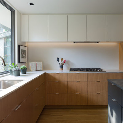 Kitchen - 1950s l-shaped medium tone wood floor and brown floor kitchen idea in Austin with a double-bowl sink, flat-panel cabinets, medium tone wood cabinets, white backsplash, paneled appliances, an island and white countertops