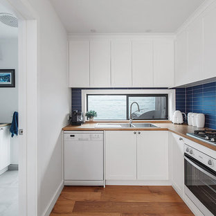 Contemporary l-shaped kitchen in Melbourne with a drop-in sink, shaker cabinets, white cabinets, wood benchtops, blue splashback, white appliances, medium hardwood floors, brown floor and brown benchtop.
