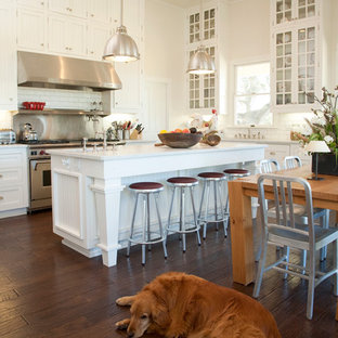 Example of a farmhouse l-shaped dark wood floor eat-in kitchen design in San Francisco with glass-front cabinets, white cabinets, white backsplash, subway tile backsplash and stainless steel appliances