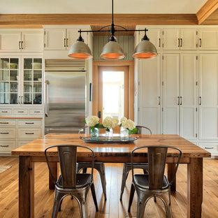Esempio di una cucina abitabile country con ante in stile shaker, ante bianche, elettrodomestici in acciaio inossidabile e pavimento in legno massello medio