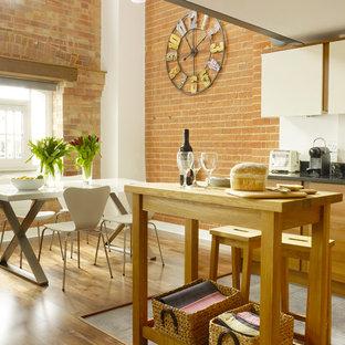 ロンドンの小さいインダストリアルスタイルのおしゃれなキッチン (アンダーカウンターシンク、フラットパネル扉のキャビネット、中間色木目調キャビネット、御影石カウンター、白いキッチンパネル、シルバーの調理設備の、磁器タイルの床) の写真