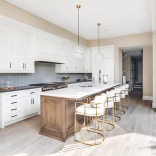 Transitional kitchen ideas - Inspiration for a transitional l-shaped light wood floor and beige floor kitchen remodel in Orange County with an undermount sink, shaker cabinets, white cabinets, gray backsplash, mosaic tile backsplash, stainless steel appliances, an island and gray countertops