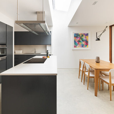 Inspiration for a mid-sized modern concrete floor and gray floor eat-in kitchen remodel in London with a double-bowl sink, flat-panel cabinets, black cabinets, stainless steel appliances and an island