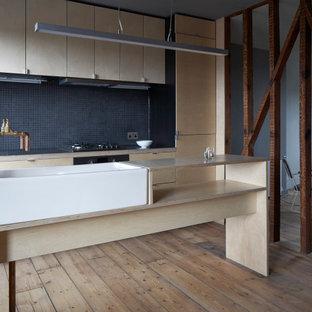 Foto di una cucina industriale con lavello stile country, ante lisce, top in legno, paraspruzzi nero, pavimento in compensato, ante in legno chiaro, paraspruzzi con piastrelle a mosaico e elettrodomestici in acciaio inossidabile